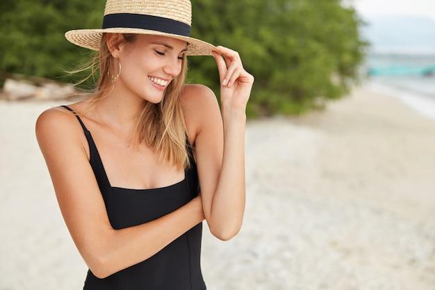 Retrato de modelo feminino jovem magro posa com expressão feliz no litoral, vestido com maiô, chapéu de verão, gosta de ser fotografado, tem uma pele saudável e pura. pessoas, positividade e descanso