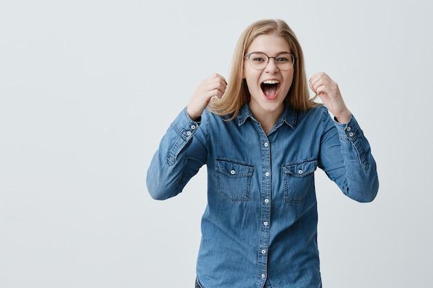 Retrato de modelo feminino muito feliz animado com cabelos loiros, óculos, camisa jeans, aperta os punhos com prazer, grita de felicidade, comemora a vitória, tem um grande triunfo. conceito de sucesso