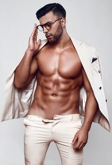 Retrato de modelo masculino elegante em um terno leve isolado em uma parede branca