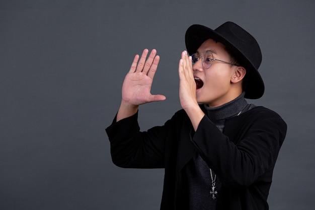 Retrato de modelo masculino posando gritar atuando na parede escura