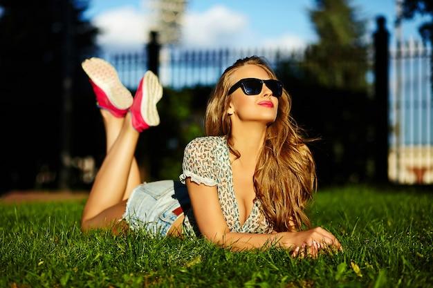 Retrato de modelo sexy engraçado mulher jovem e bonita elegante sorridente menina em pano moderno brilhante com corpo perfeito para banhos de sol ao ar livre, deitado no parque na grama verde em shorts jeans em copos