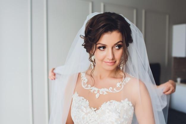Retrato de modelos de moda com buquê de flores, mulher bonita maquiagem de noiva e penteado