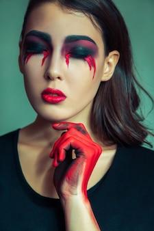 Retrato de monstro estranho com maquiagem suja de bagunça no rosto chorando mulher com sangue vermelho