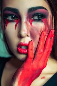 Retrato de monstro estranho com maquiagem suja de bagunça no rosto. mulher chorando com lágrimas de sangue vermelhas e mão. conceito de halloween sobre fundo verde. foto do estúdio, olhos castanhos escuros.