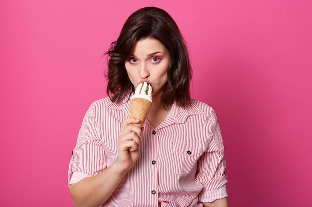 Retrato de morena concentrada grave segurando sorvete, provando, olhando diretamente para a câmera, com maquiagem brilhante, vestindo roupas casuais, isolado sobre rosa