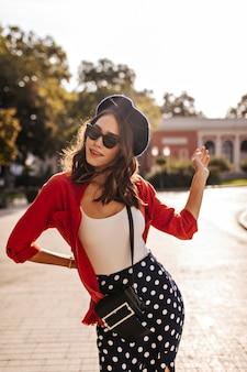 Retrato de morena fashion em roupa de estilo francês de boina, top branco, camisa e saia de bolinhas lindas posando contra a parede da cidade iluminada pelo sol durante o verão