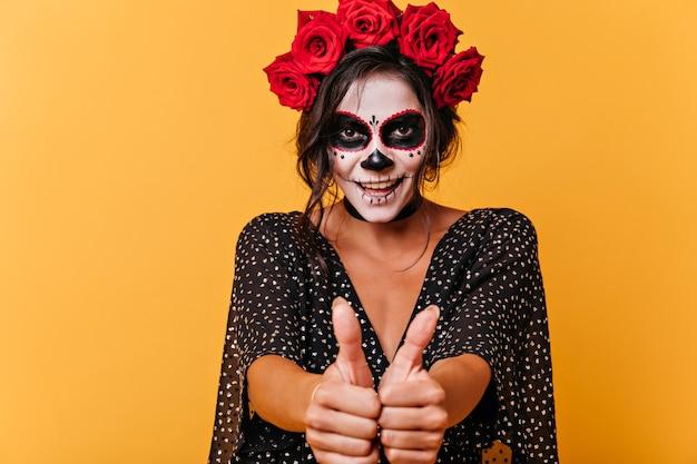 Retrato de morena manhosa de olhos castanhos aparecendo os polegares. menina com coroa de rosas e arte facial em forma de caveira sorrindo.