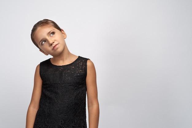Retrato de morena menina pensativa em um vestido preto. linda criança indecisa duvidosa, olhando para os olhos pensativos, com uma expressão confusa pensando em algo.