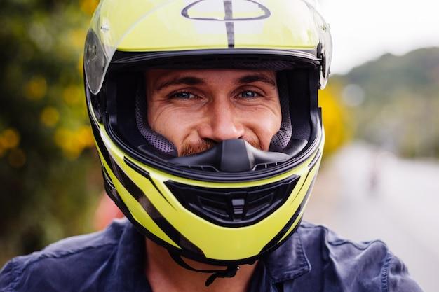 Retrato de motociclista com capacete amarelo em motocicleta na beira de uma estrada movimentada na tailândia