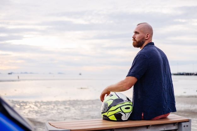 Retrato de motociclista com capacete amarelo sentado em um banco no calçadão da tailândia, ao pôr do sol