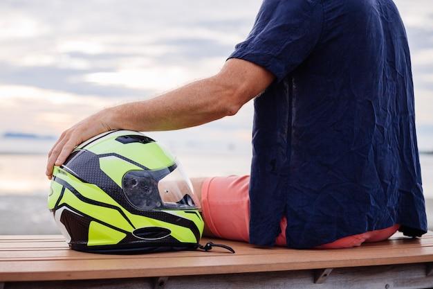 Retrato de motociclista com capacete amarelo sentado em um banco no calçadão na tailândia, ao pôr do sol
