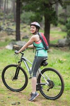 Retrato de motociclista feminina na floresta