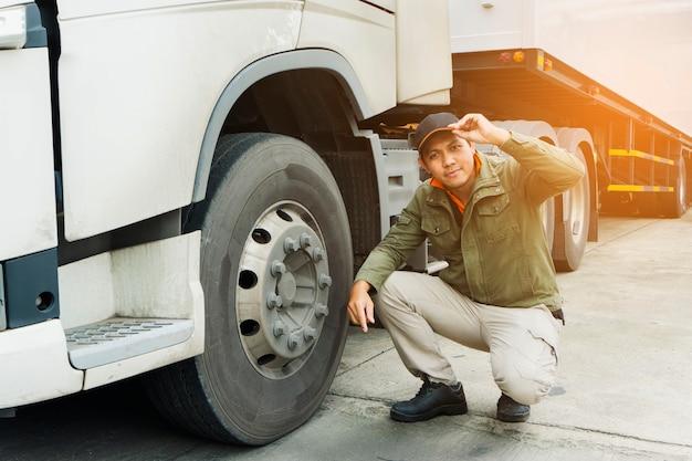 Retrato de motorista de caminhão, inspecionando a segurança das rodas do caminhão