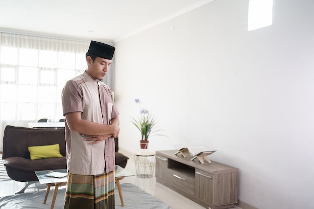 Retrato de muçulmano asiático orando dobrando o braço em frente a um baú em casa