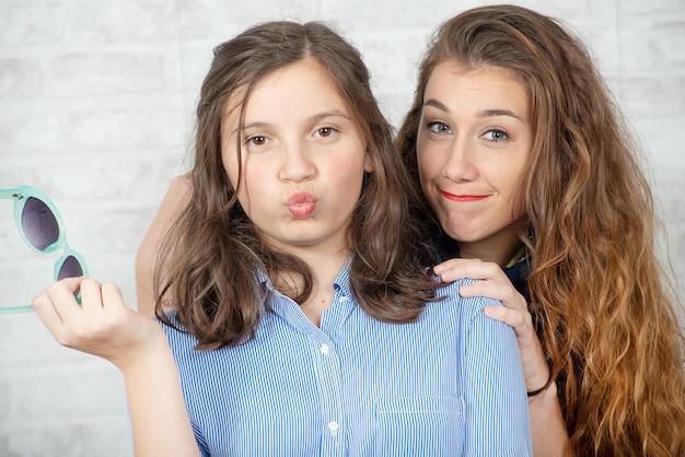 Retrato de muito lindo charmoso adorável com cabelos longos menina e seu amigo mais velho