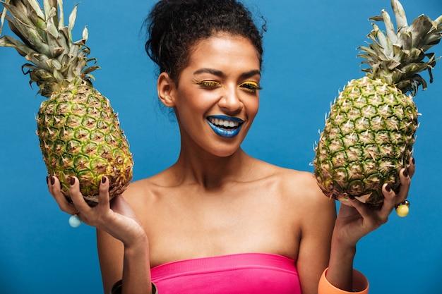 Retrato de mulata alegre com maquiagem elegante piscando enquanto segura dois abacaxis suculentos em ambas as mãos isoladas, sobre a parede azul