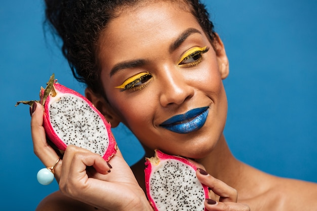 Retrato de mulata incrível com maquiagem brilhante, desfrutando de frutas exóticas pitaya cortadas ao meio e olhando de lado isolado, sobre parede azul