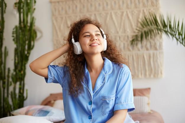 Retrato de mulata jovem encaracolado simpático, amplamente sorri com os olhos fechados, ouvindo música favorita em fones de ouvido, aproveitando a manhã de domingo, parece feliz e alegre.