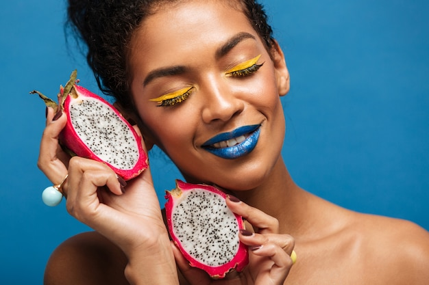 Retrato de mulata morena com maquiagem brilhante, desfrutando de pitaya maduro cortado ao meio com os olhos fechados e segurando frutas no rosto, ao longo da parede azul