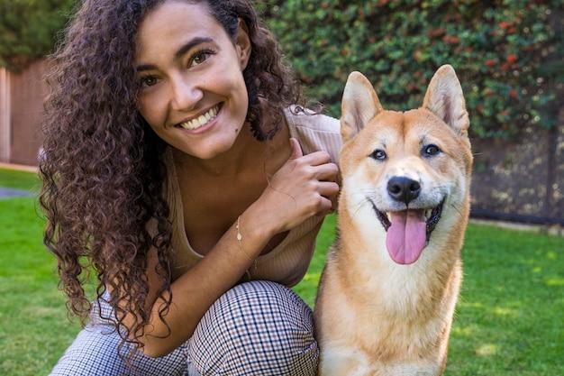 Retrato de mulher abraçando e beijando seu cachorro no jardim
