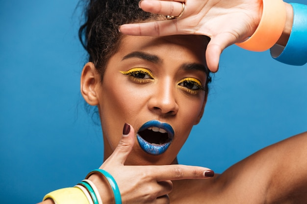 Retrato de mulher adorável elegante com maquiagem colorida e cabelos cacheados em coque gesticulando na câmera com sorriso, isolado sobre a parede azul
