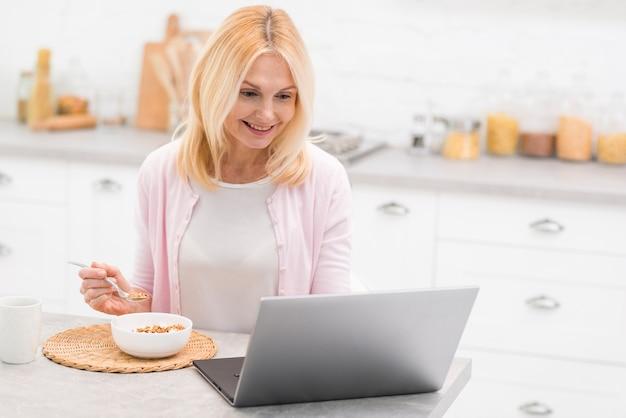 Retrato de mulher adorável sênior tomando café da manhã