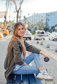 Retrato de mulher adorável, sentado num banco, segurando o café e ouvir música na rua durante o dia.