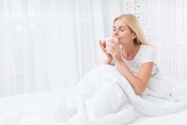 Retrato de mulher adorável tomando café na cama