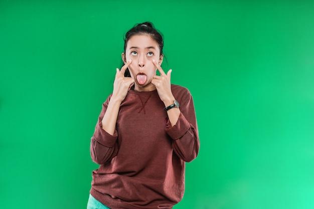 Retrato de mulher adulta de expressão engraçada louca e a língua sai da boca isolada na parede verde