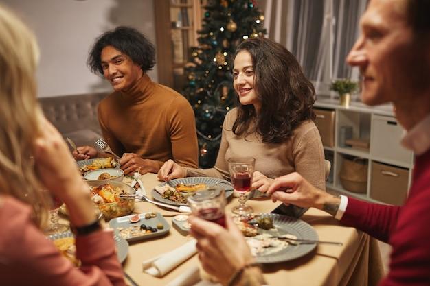 Retrato de mulher adulta do oriente médio sorrindo alegremente enquanto janta com amigos e família dentro de casa.