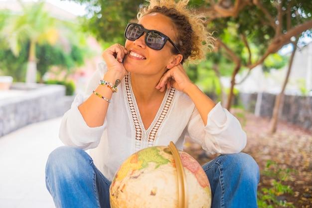 Retrato de mulher adulta feliz sorrindo alegre ao ar livre no parque com globo terrestre pensando e sonhando próximo destino de viagem de férias para férias