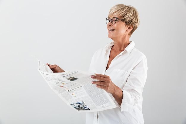 Retrato de mulher adulta feliz usando óculos, sorrindo e lendo jornal isolado sobre uma parede branca em estúdio