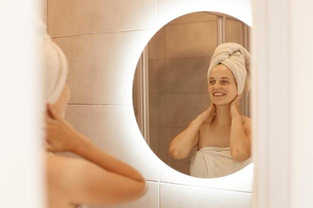 Retrato de mulher adulta jovem fresca feliz com a pele perfeita, olhando no reflexo no espelho com um sorriso encantador, depois do banho, tocando seu pescoço, fazendo procedimentos de beleza.