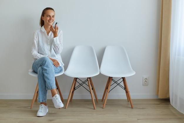 Retrato de mulher adulta jovem sorridente, sentado na cadeira, segurando o telefone inteligente, pedindo assistente de voz no celular, dando tarefa, gravando mensagem, expressando emoções positivas.