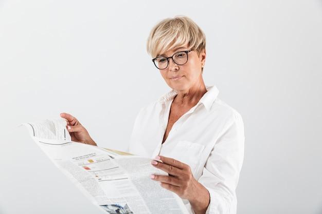 Retrato de mulher adulta madura usando óculos, lendo jornal isolado sobre uma parede branca em estúdio