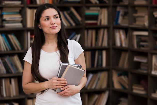 Retrato de mulher adulta segurando livros