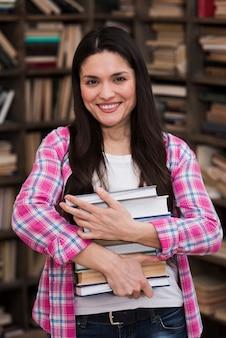 Retrato, de, mulher adulta, segurando, pilha livros