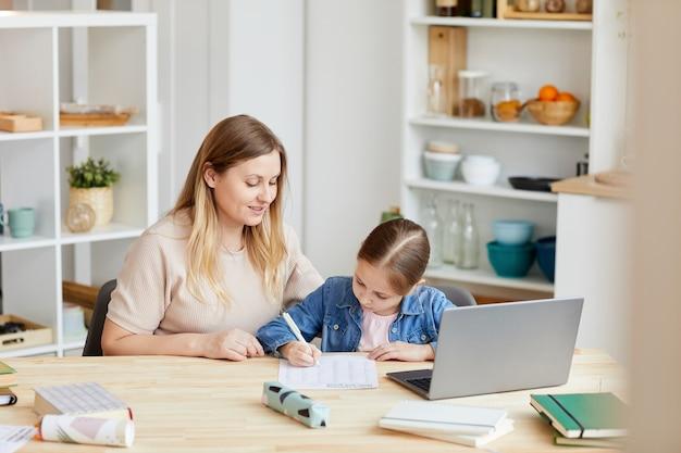 Retrato de mulher adulta sorridente, ajudando a menina a fazer o dever de casa ou a estudar em casa num interior acolhedor, copie o espaço