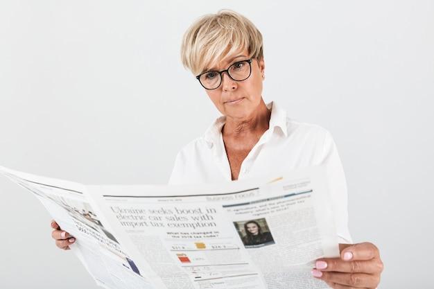 Retrato de mulher adulta tensa usando óculos, lendo jornal isolado sobre uma parede branca em estúdio
