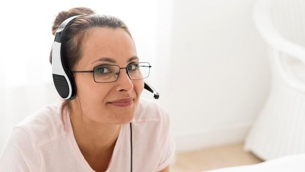 Retrato de mulher adulta trabalhando com fones de ouvido