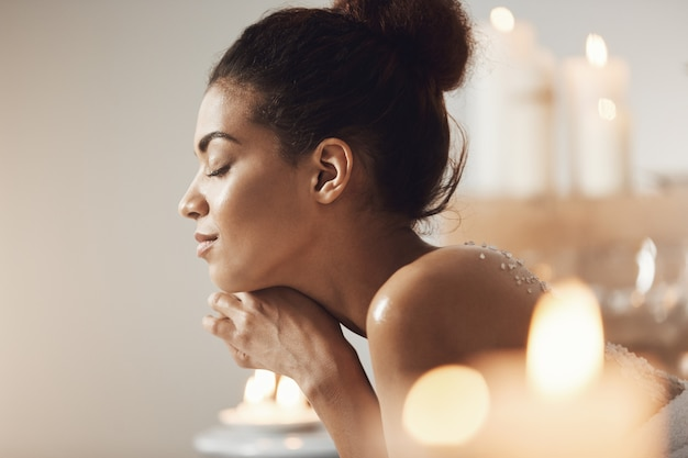 Retrato de mulher africana contente relaxante com os olhos fechados no salão spa.
