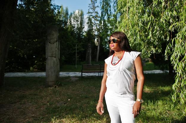 Retrato de mulher africana em óculos de sol na luz do sol no parque verde