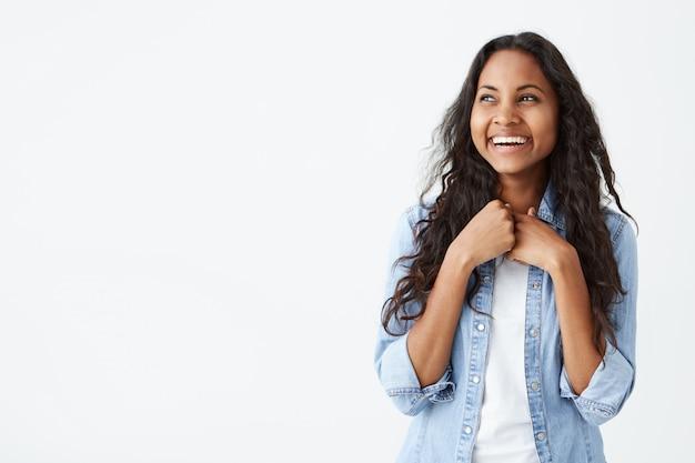 Retrato de mulher afro-americana carismática e encantadora, com longos cabelos ondulados, vestindo camisa jeans elegante, sorrindo amplamente, sendo animado para obter surpresa do namorado, parecendo feliz.