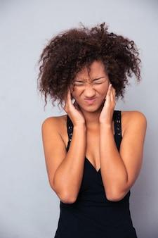 Retrato de mulher afro-americana cobrindo as orelhas na parede cinza