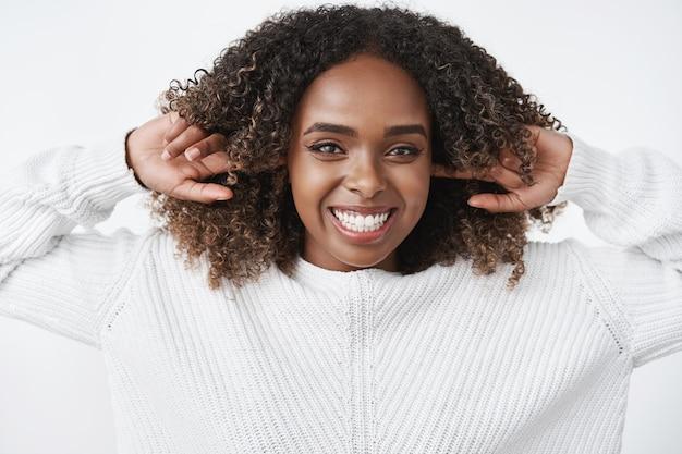 Retrato de mulher afro-americana despreocupada, feliz e alegre, carismática, rindo e sorrindo alegremente fecha as orelhas com o dedo indicador e olha encantado para a frente