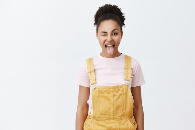 Retrato de mulher afro-americana feliz e despreocupada de macacão amarelo sobre uma camiseta da moda, mostrando a língua e piscando alegremente