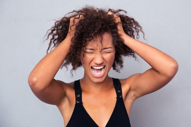 Retrato de mulher afro-americana gritando por cima de uma parede cinza