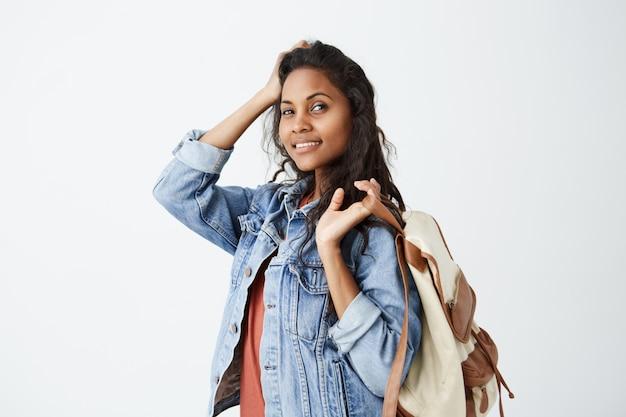 Retrato de mulher alegre bonita de pele escura com cabelos ondulados, com olhos escuros encantadores e sorriso atraente posando sobre parede branca, vestindo jaqueta jeans com mochila no ombro