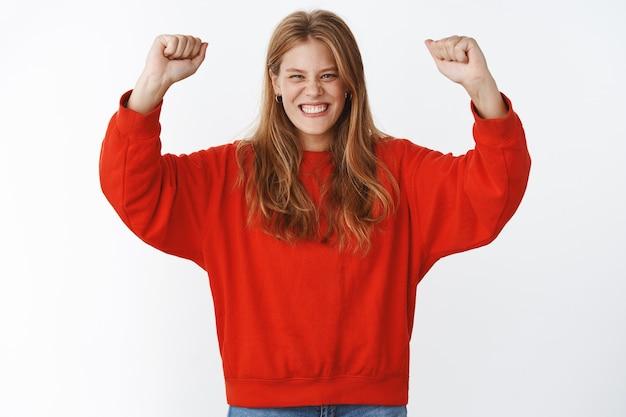 Retrato de mulher alegre e otimista com sardas fofas e cabelos louros levantando as mãos acima da cabeça em alegria e triunfo, sendo a vencedora comemorando o sucesso e a vitória sorrindo, regozijando-se com um suéter vermelho