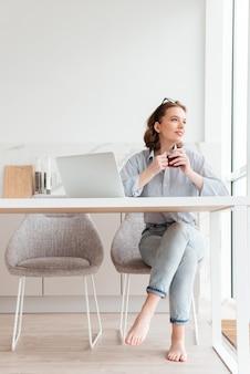 Retrato de mulher alegre em camisa listrada e calça jeans segurando a xícara de chá enquanto está sentado na cadeira macia na cozinha